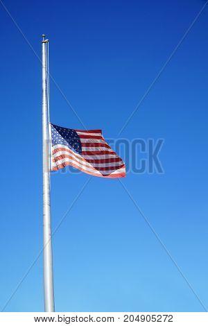 half mast American flag under blue sky