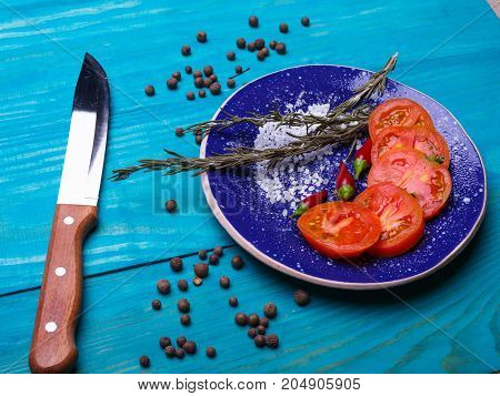 Fresh sliced tomatoes in a plate on a wooden background. Healthy lifestyle