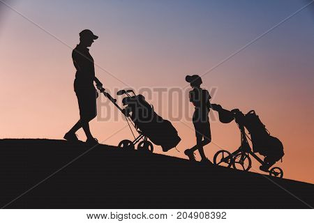 silhouettes of man with his son golfers walking with bags on golf course at sunset