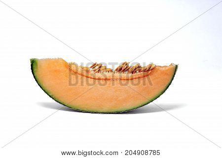 Pieces of orange Melon or cantaloupe fruit show flesh and seeds on white background.