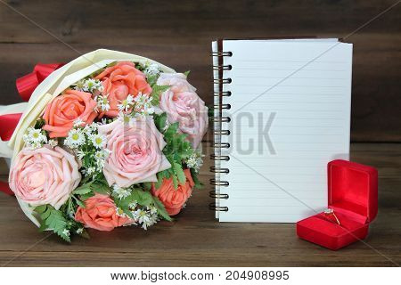 Wedding ring Diamond ring in red box with Wedding bouquet from pink and orange roses and a white book on wooden background copy space for text.