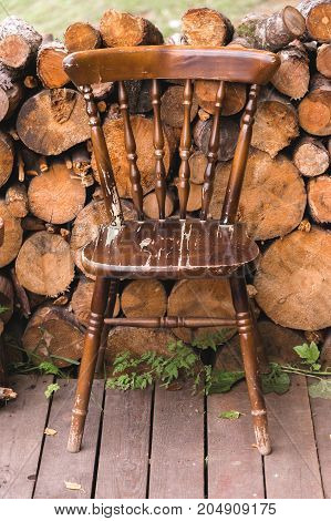 old vintage chair made of wood on the background of wood logs firewood