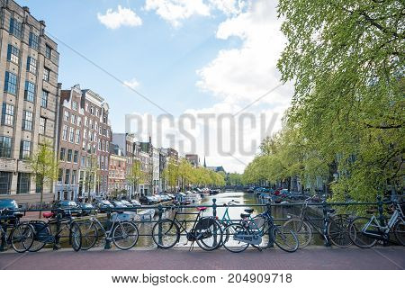 Bicycles On A Bridge Over The Canals Of Amsterdam. The Netherlands