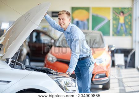 A young couple chooses a new car in the showroom. The concept of buying a new car.