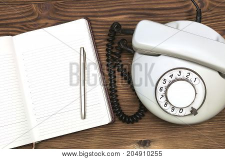 Old telephone open phone book with blank pages with copy space and pen on wooden table surface. Contact us.
