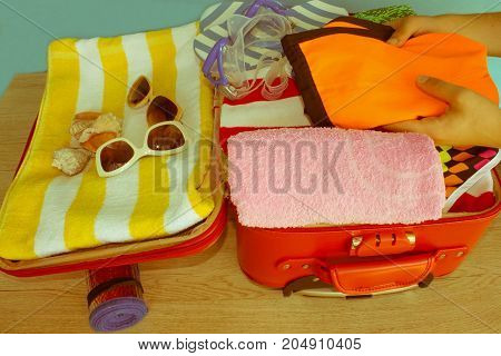 Young woman packing suitcase. Woman packing stuff into suitcase at home. Travel and vacation concept - Retro color