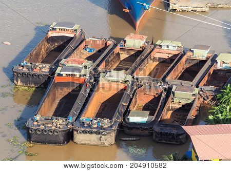 The sand barges floating in the Chao Phraya River Park. Bangkok, Thailand.