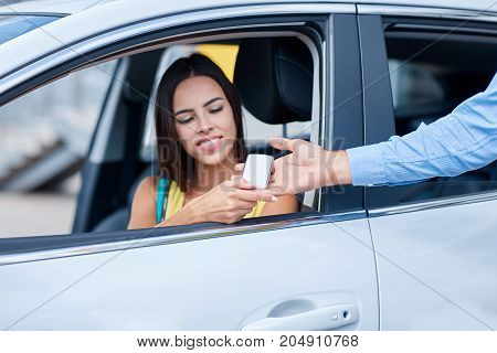 The seller of cars transfers keys from the new car to the woman. Conceptual image