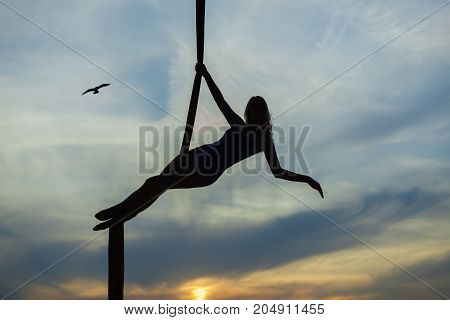 Woman aerial acrobat on the background of the setting sun she does the tricks.