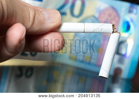 Quit smoking save money broken cigar in man hand