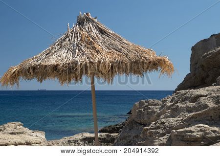 Sunshade on the Greek rocky beach on Rhodos island