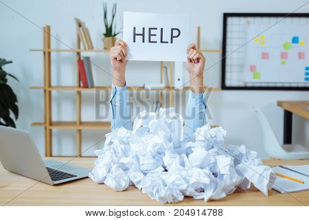 Fed up. Experienced worker sitting at his workplace and raising arms while demonstrating paper shit with word on it