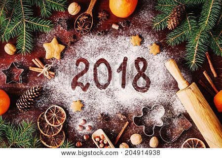 Happy New Year 2018 written on flour and Christmas Decorations Gingerbread cookies, cinnamin, oranges, spices, nuts and cookie cutters on wooden background. Christmas card, New Year greeting card