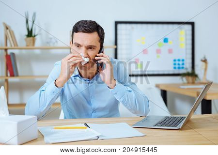 It is me. Pessimistic brunette male being at work and wiping nose while holding telephone