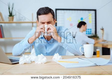 I am sick. Pessimistic man keeping eyes closed and holding serviette in both hands while putting elbows on the table