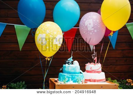 Birthday cake with candles and colorful balloons in background