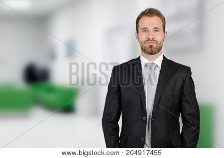Portrait Of Young Businessman Standing In Office