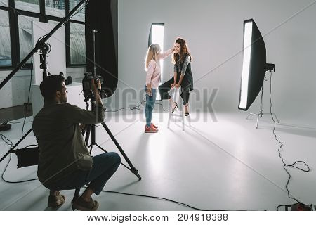 professional photographer makeup artist and beautiful model on fashion shoot in photo studio with lighting equipment