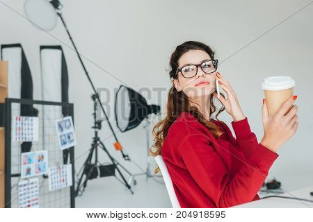 Designer With Smartphone In Office