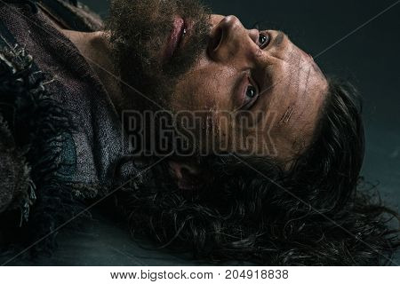Halloween zombie lying on paving asphalt. Vampire hipster with red blood outdoors. Holiday celebration concept. Man with bloody beard and hair. War soldier with wounds on face.