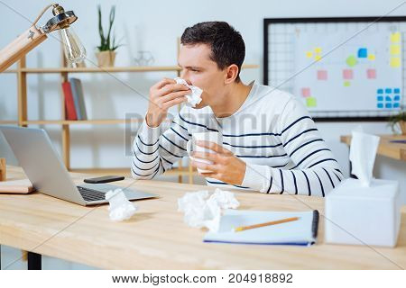 Sickness in office. Ill male person holding cup in left hand and wiping nose while working with computer