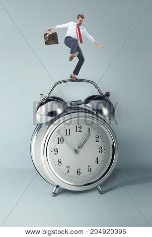 Businessman balancing over alarm clock. Collage about tardiness and lack of time. concept of business acceleration