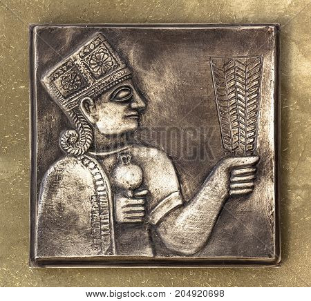 An ancient Mayan relief on bronze tablet with golden tones.