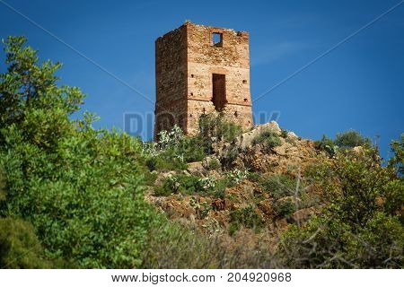 Long shot of antique stone tower over hill near sea