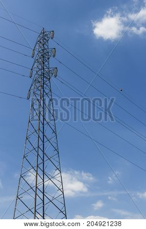 Pylon with blue sky and clouds in the background.