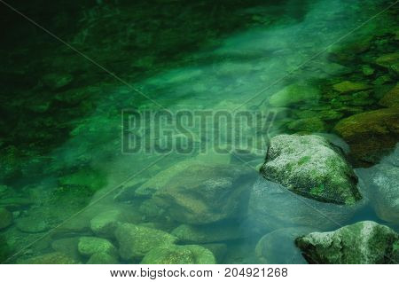 Spooky rocks covered with moss in dark green water (horror concept)