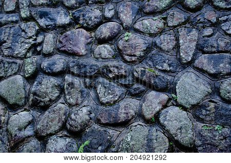 Old dark wet stones as an abstract stone background or stone texture