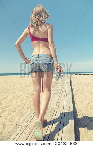 Woman holding vintage film camera on the beach.