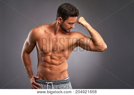 A handsome young sportsman showing his biceps