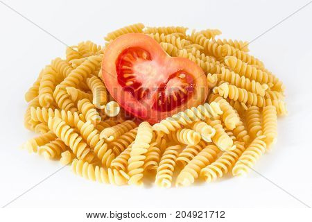 Bunch of pasta with tomato cut in half on a white background.