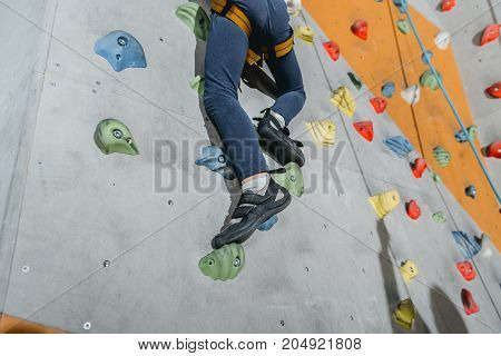 Cropped shot of a little boy in harness climbing a wall with grips at gym