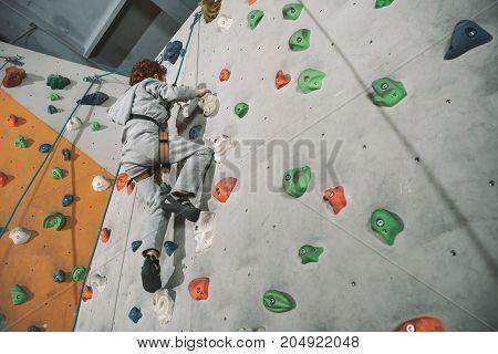 Red-headed Boy Climbing Wall