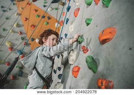 Little Boy Climbing Wall At Gym