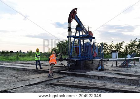 Two engineers at work on an east European oil well