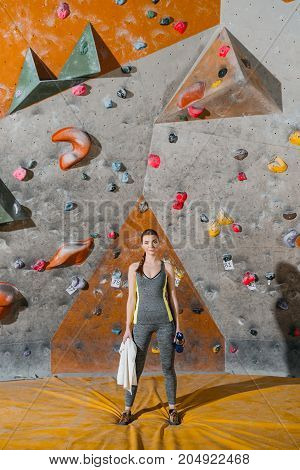 Young Woman In Front Of Climbing Wall