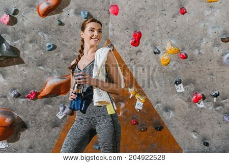 Sportive Woman In Front Of Climbing Wall