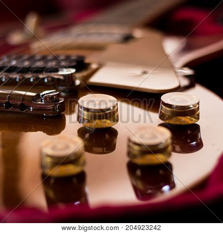 Closeup of tone knobs and volume of an electric guitar.