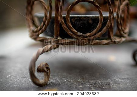 Extreme close-up of wrought iron planter attacked by rust.