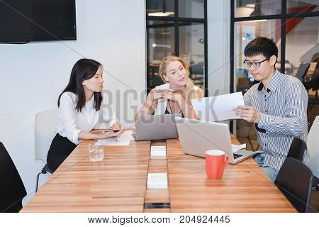 Group Of Business People Meeting In A Meeting Room, Sharing Their Ideas