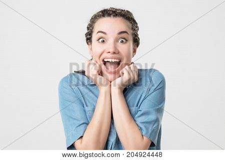 Delighted caucasian woman opening mouth in surprise. She is amazed with news or winning or sales. Positive facial emotion concept in young age.
