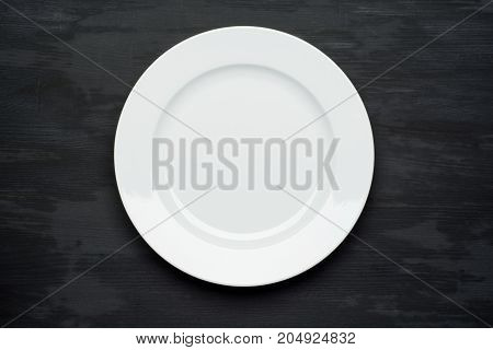 Empty plate on dark black wooden background. Top view with copy space.