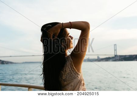 Cruise ship vacation woman enjoying travel vacation at sea relaxed. Free carefree happy girl looking at ocean with open arms in freedom pose.