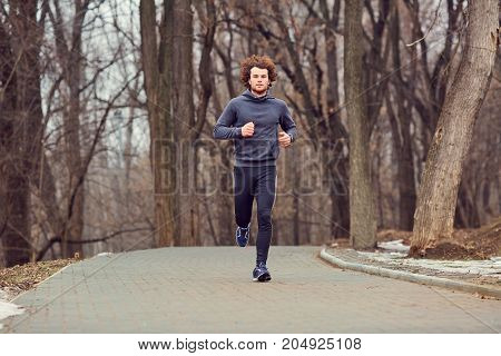 A young male runner runs in the park in the winter.