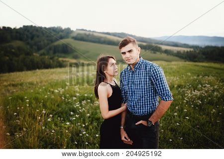 girl is holding the boyfriend of her lover, lovers are standing on the background of sky and mountains, concept love, dates, a journey together.