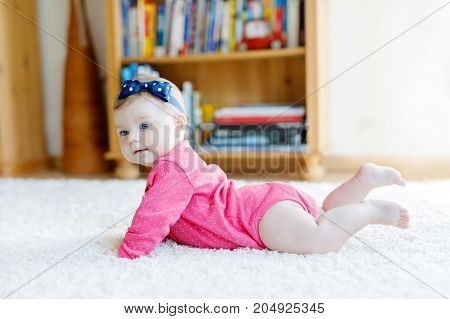 Baby girl with blue eyes lying on belly. Nursery for children. Textile and bedding for kids. Happy cute new born girl. child with headband