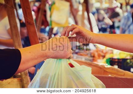Farmer vendor hands over plastic bag filled with fresh vegetables to buyer. Woman shopping vegetables at the market.